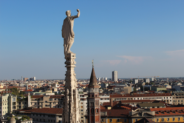 Statue up in the Duomo di Milano and the city from above